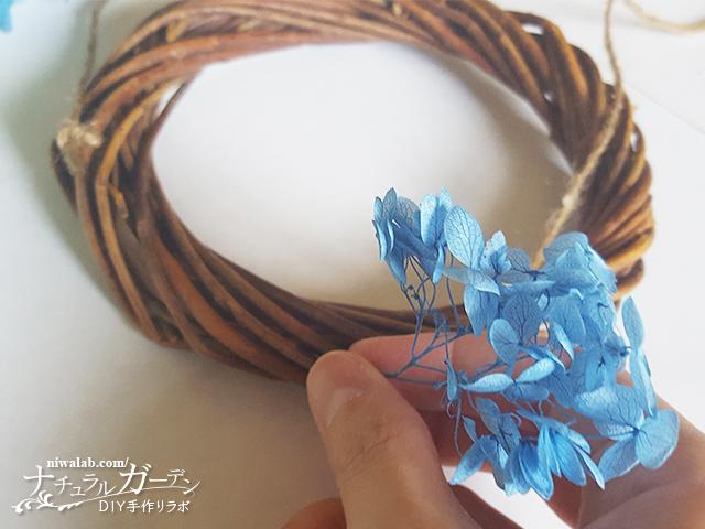 リースに花を挿し込む